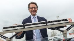 Andreas Scheuer (CSU), Bundesverkehrsminister steht nach einer Pressekonferenz, steht zum Start einer Machbarkeitsstudie für eine Magnetschwebebahn hinter einem Modell am Münchner Flughafen.  | Bild:dpa-Bildfunk/Peter Kneffel