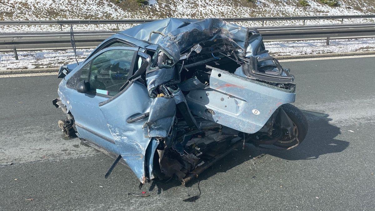 Ein zerstörter blauer Kleinwagen.