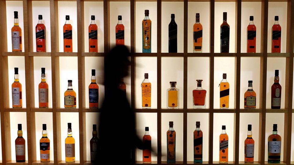 Eine Frau geht an einem Regal mit Whiskys vorbei.
