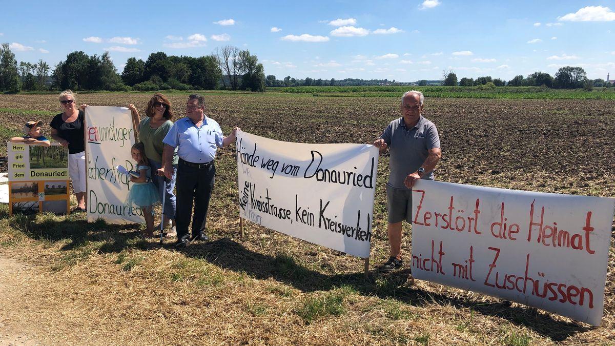 """Menschen neben Bannern, auf denen unter anderem steht: """"Zerstört die Heimat nicht mit Zuschüssen"""""""