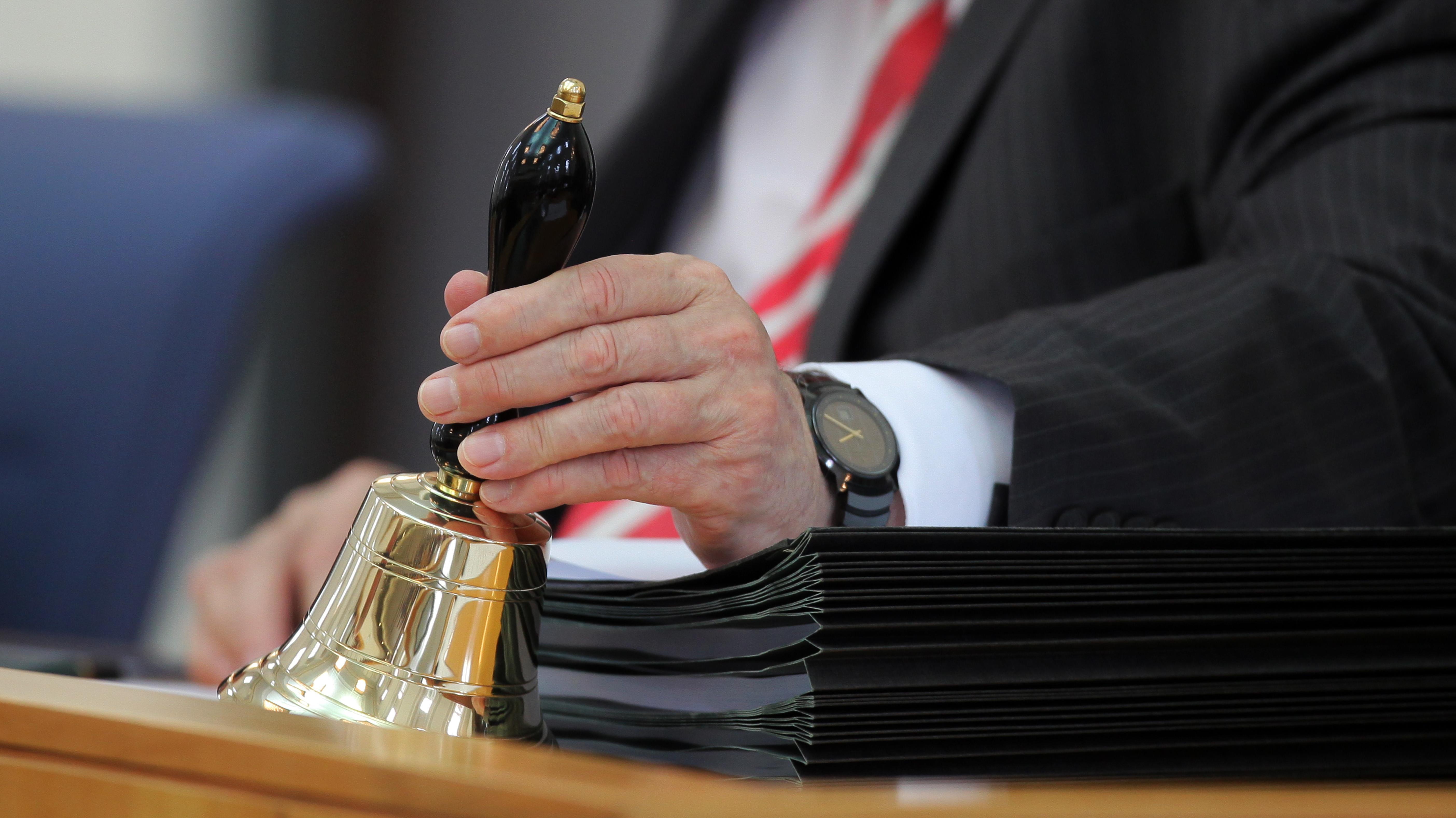 Landtagspolitiker greift zur Glocke, um auf abgelaufene Redezeit aufmerksam zu machen