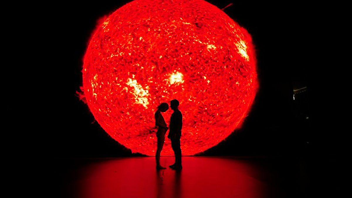 """Ein Paar steht vor einem rotglühenden Kreis, der aussieht wie ein Sonnenball (Filmszene aus """"Ema"""")"""