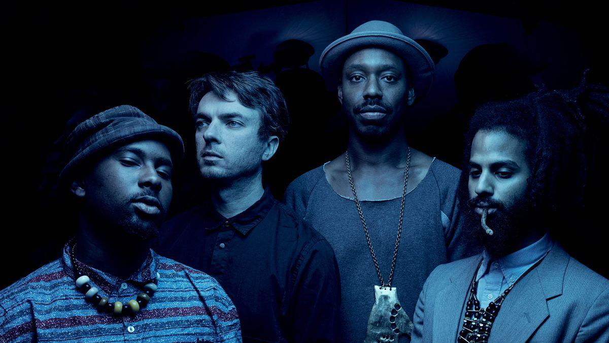 Vier junge Männer in blauem Licht blicken in unterschiedliche Richtungen