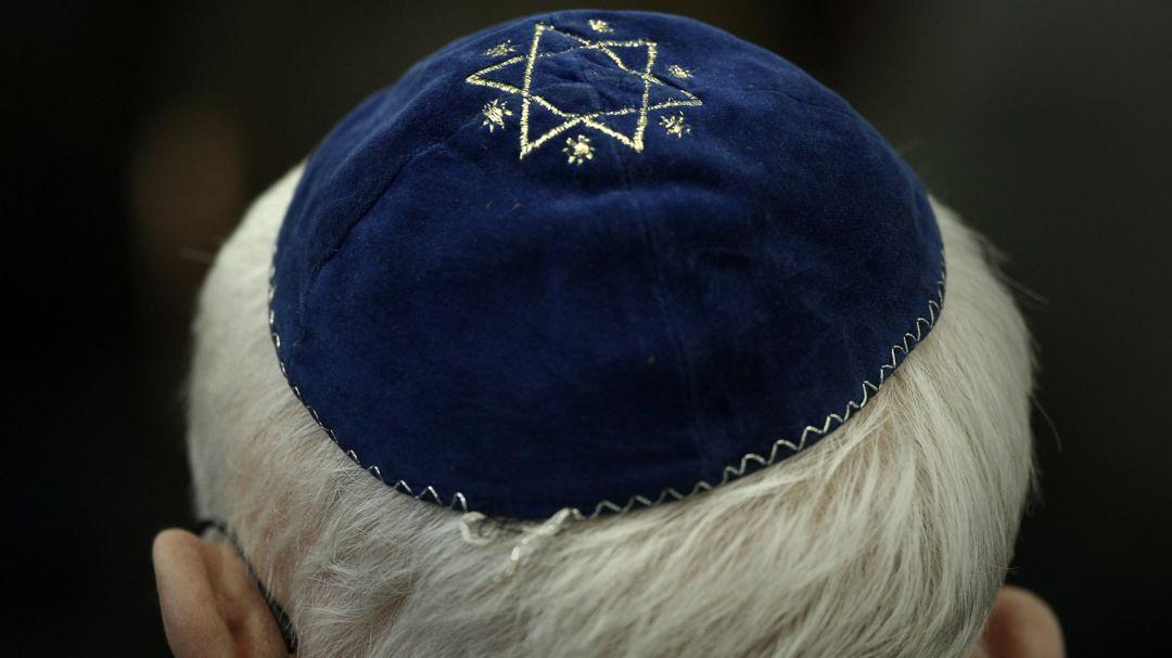 Ein Mann trägt in einer Synagoge eine Kippa mit einem aufgenähtem Davidstern.