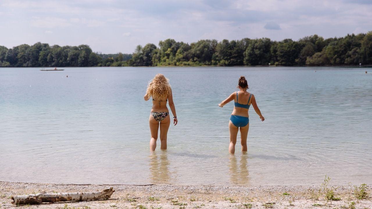 Zwei Frauen gehen in einen Badesee.