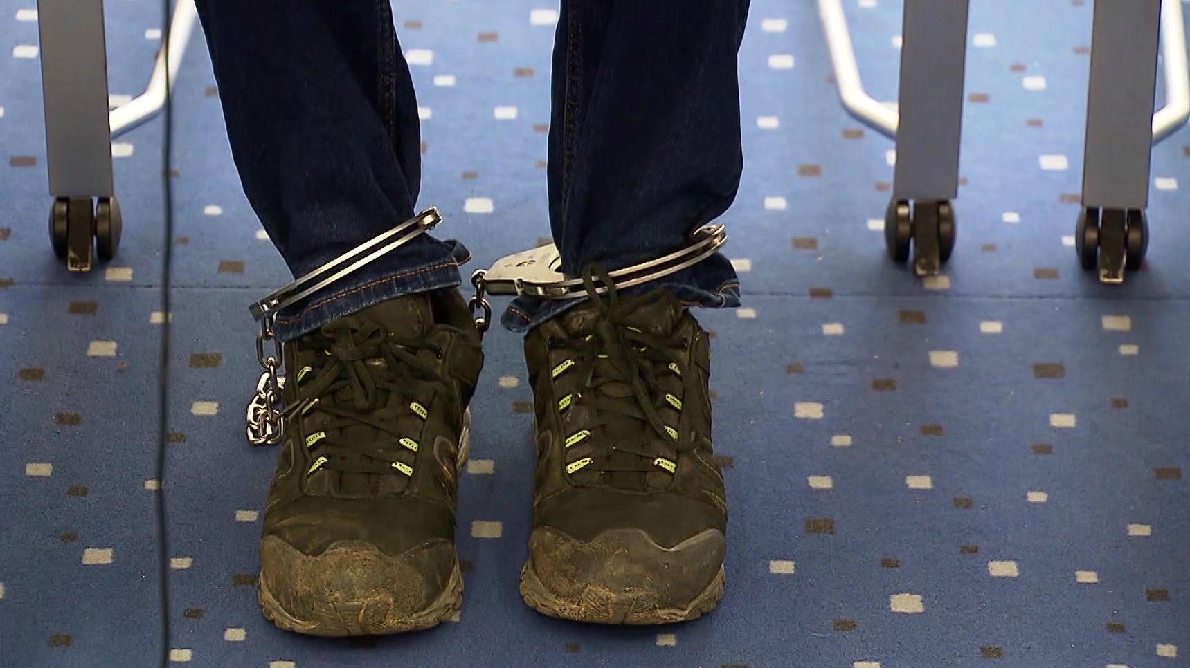 Ein Angeklagter sitzt mit Fußfesseln im Gerichtssaal