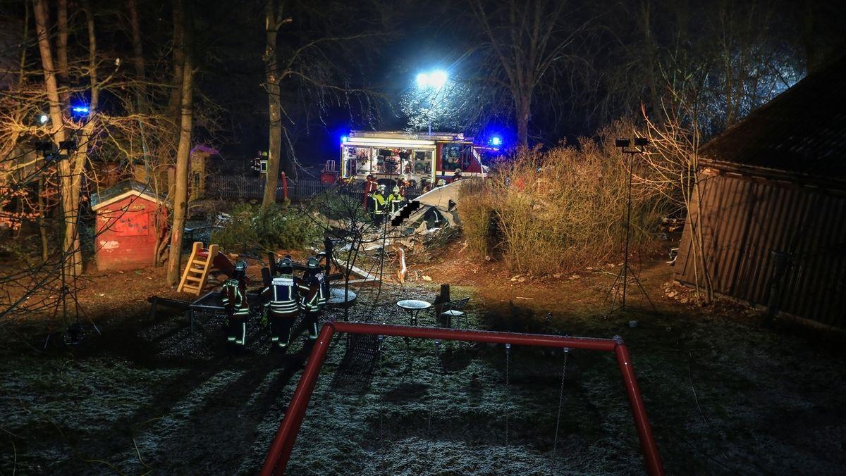 Einsatzkräfte der Feuerwehr stehen neben einem abgestürzten Flugzeug.