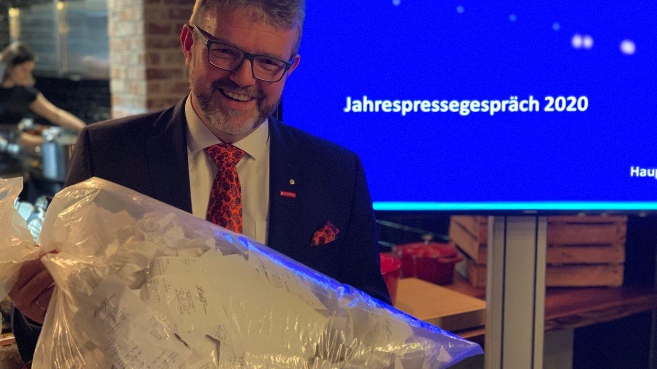 Ein Mann hält einen Müllsack in der Hand, in dem er viele Kassenbons gesammelt hat.