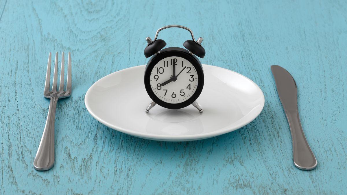 Wecker steht auf leerem Teller, Besteck liegt auf dem Tisch daneben.