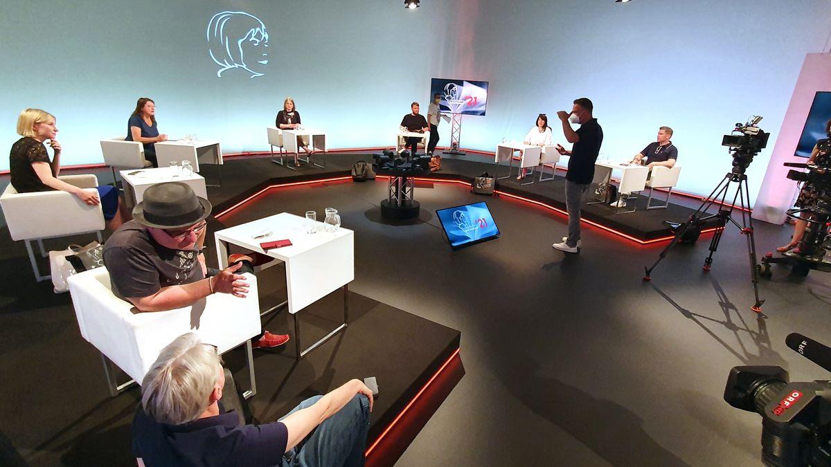 Menschen sitzen in Sesseln in einem TV-Studio
