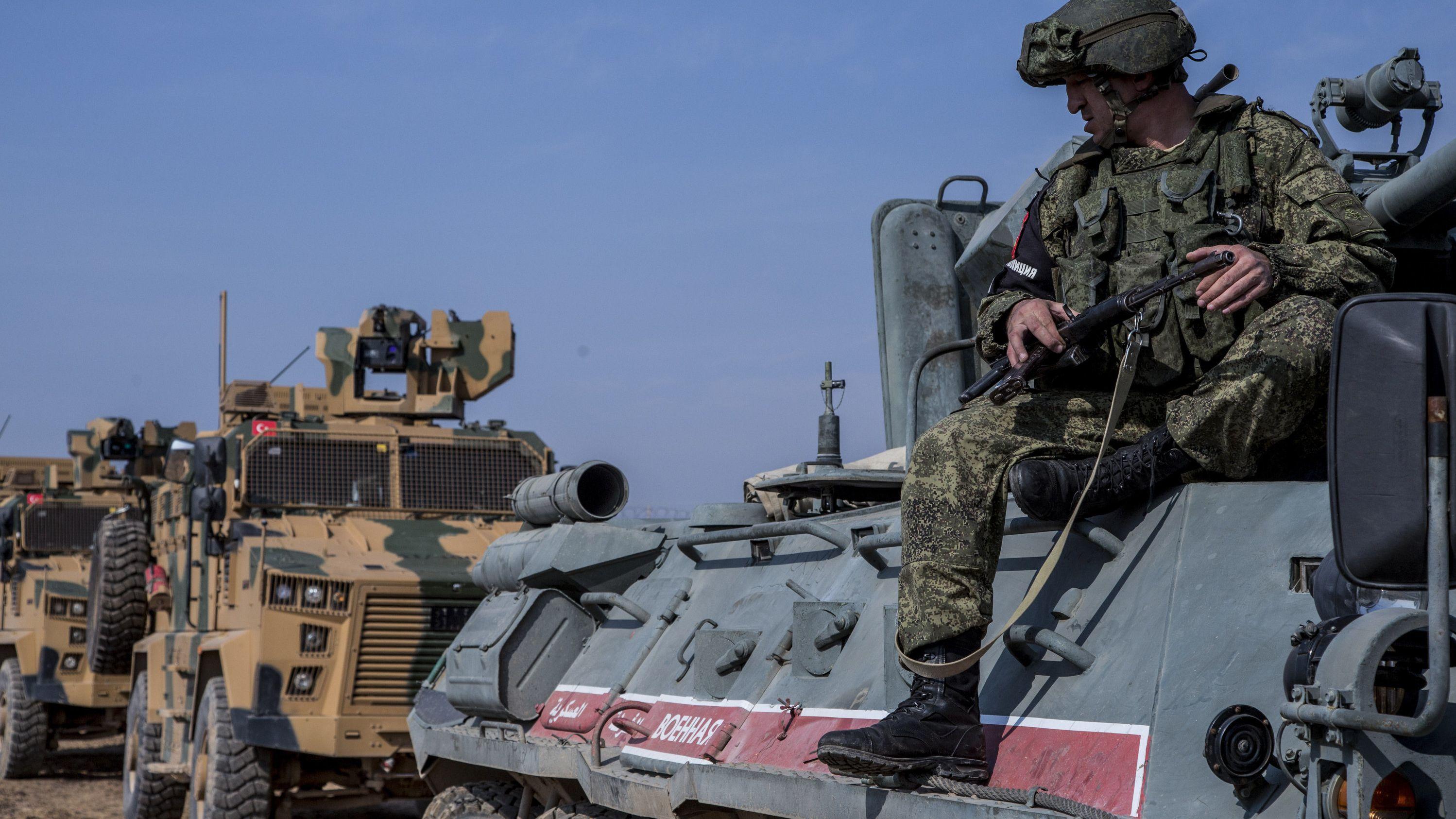 Ein bewaffneter Soldat sitzt auf einem Militärfahrzeug.