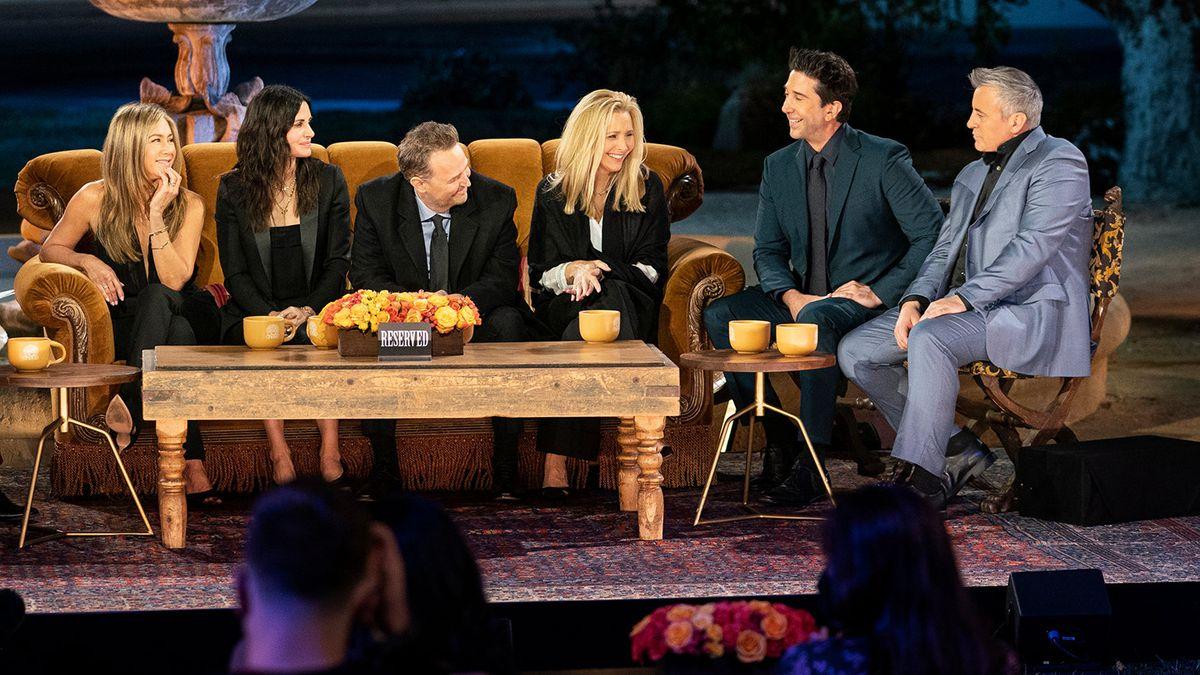 Sechs Personen sitzen auf Sofas und Stühlen