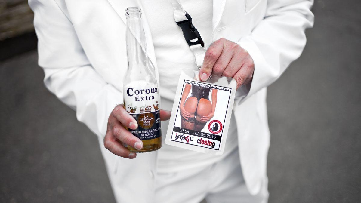 Mann im weißen Anzug hält eine Corona-Bierflasche und eine Partyeinladung in die Kamera, auf der die nackten Pobacken einer Frau im Lackkorsett abgebildet ist.