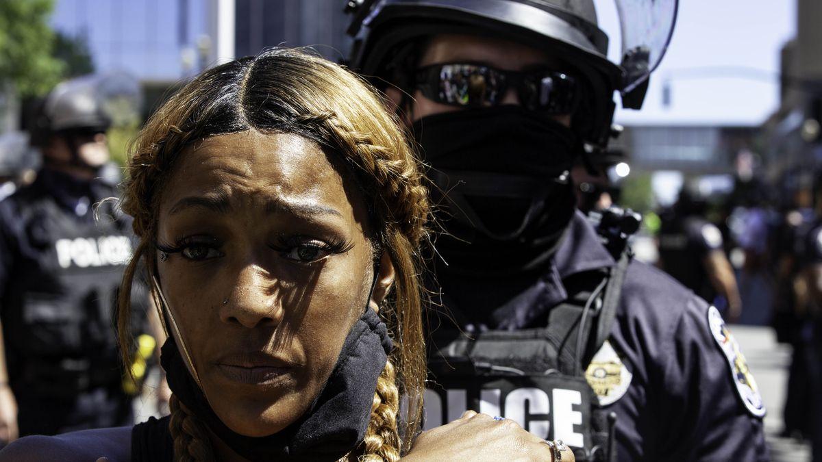 Ein Polizist in Einsatzausrüstung und eine schwarze Frau.