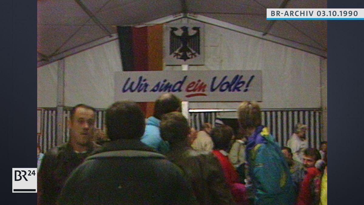"""Menschen in einem Zelt, Banner mit der Aufschrift """"Wir sind ein Volk!"""""""