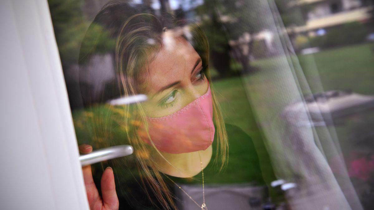 Eine junge Frau steht am Fenster und blickt traurig in einen Innenhof