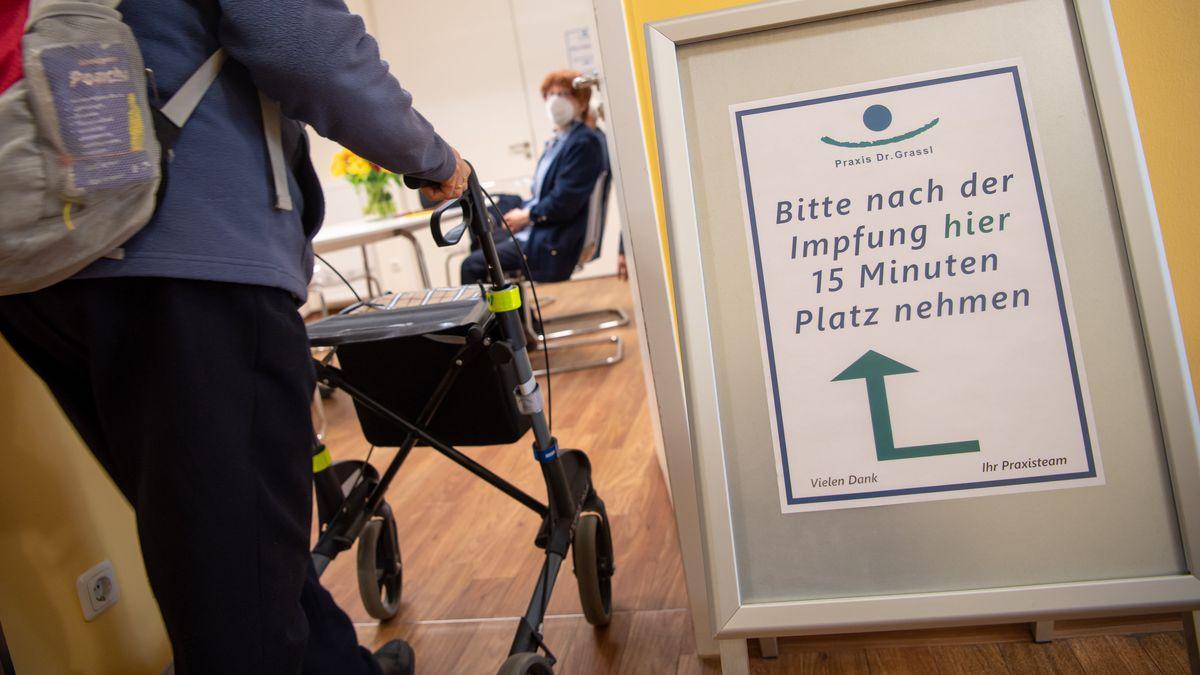 """Ein Schild mit der Aufschrift """"Bitte nach der Impfung hier 15 Minuten Platz nehmen"""" steht zum Start der Corona-Impfungen in bayerischen Hausarztpraxen vor einem Ruhezimmer in einer Hausarzt-Praxis."""