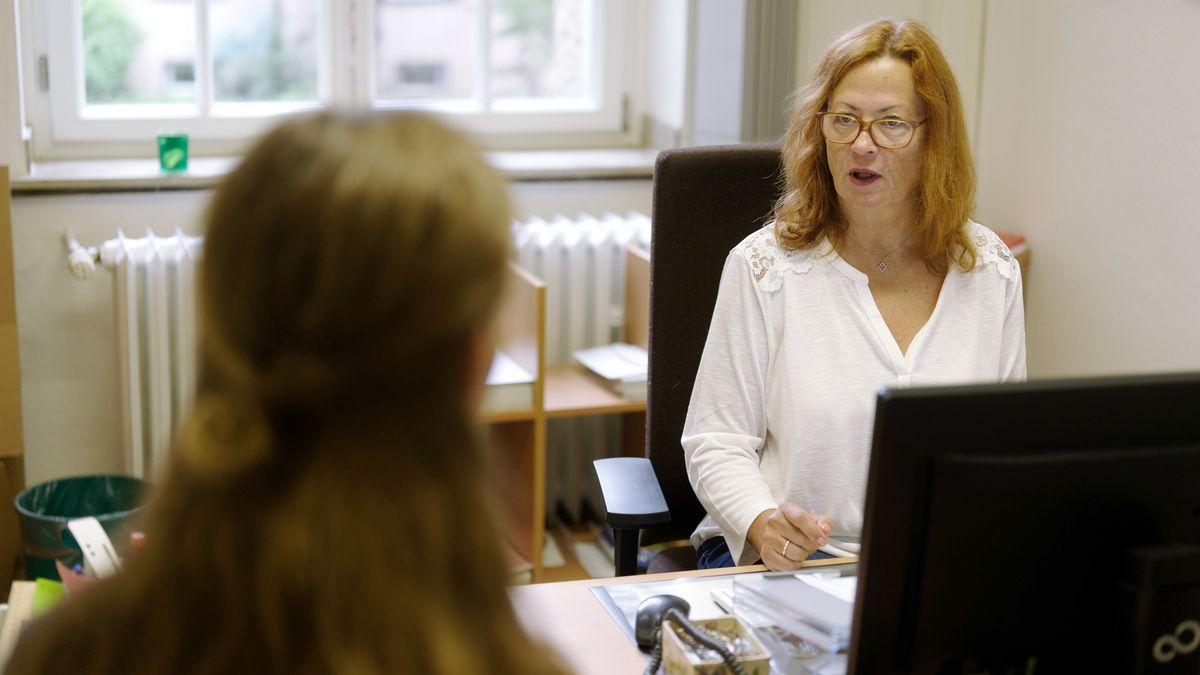 Amtsstube für Kirchenaustritte (Köln) / Standesbeamtin hinter dem Schreibtisch, gegenüber eine Dame, die aus der Kirche austreten möchte