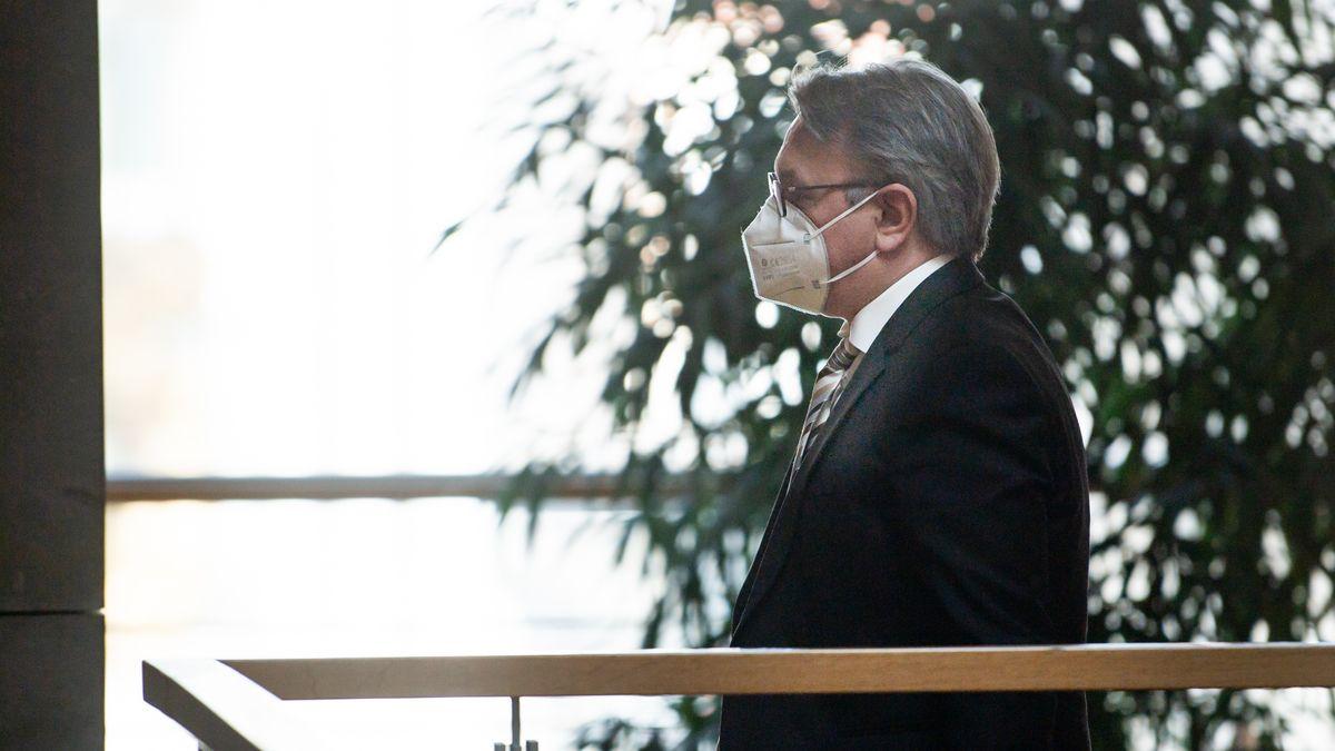 Georg Nüßlein geht über einen Flur zu seinem Bundestagsbüro, während dieses durchsucht wird.