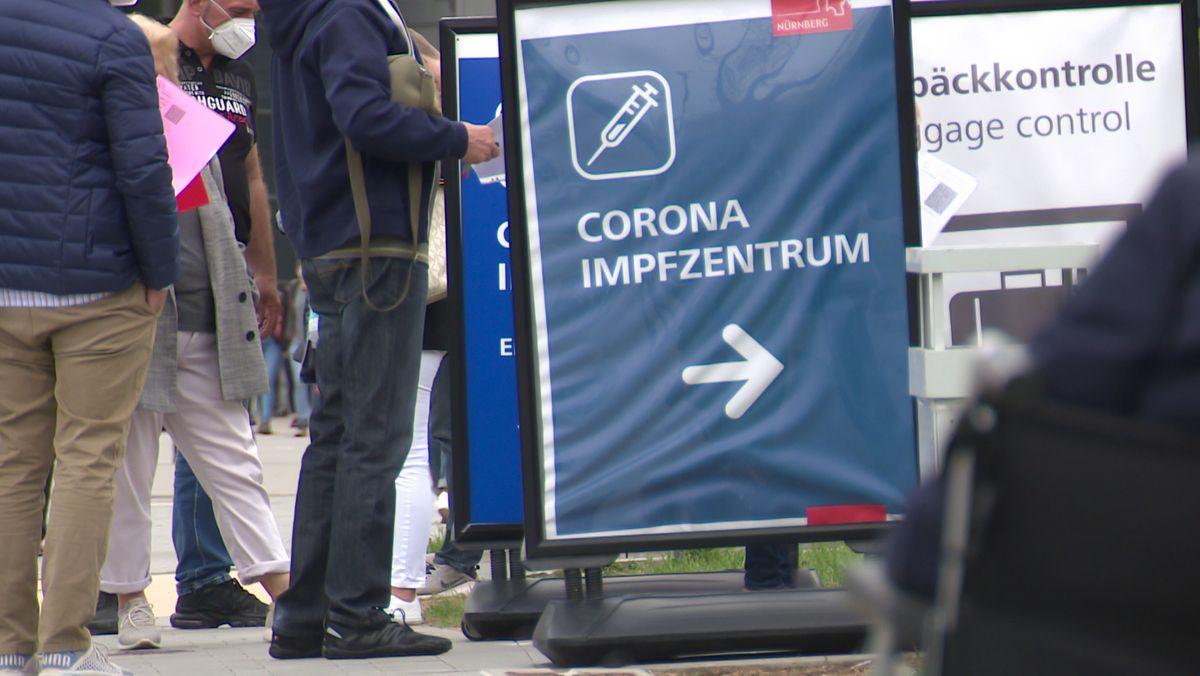 Menschen stehen vor einem Corona-Impfzentrum.