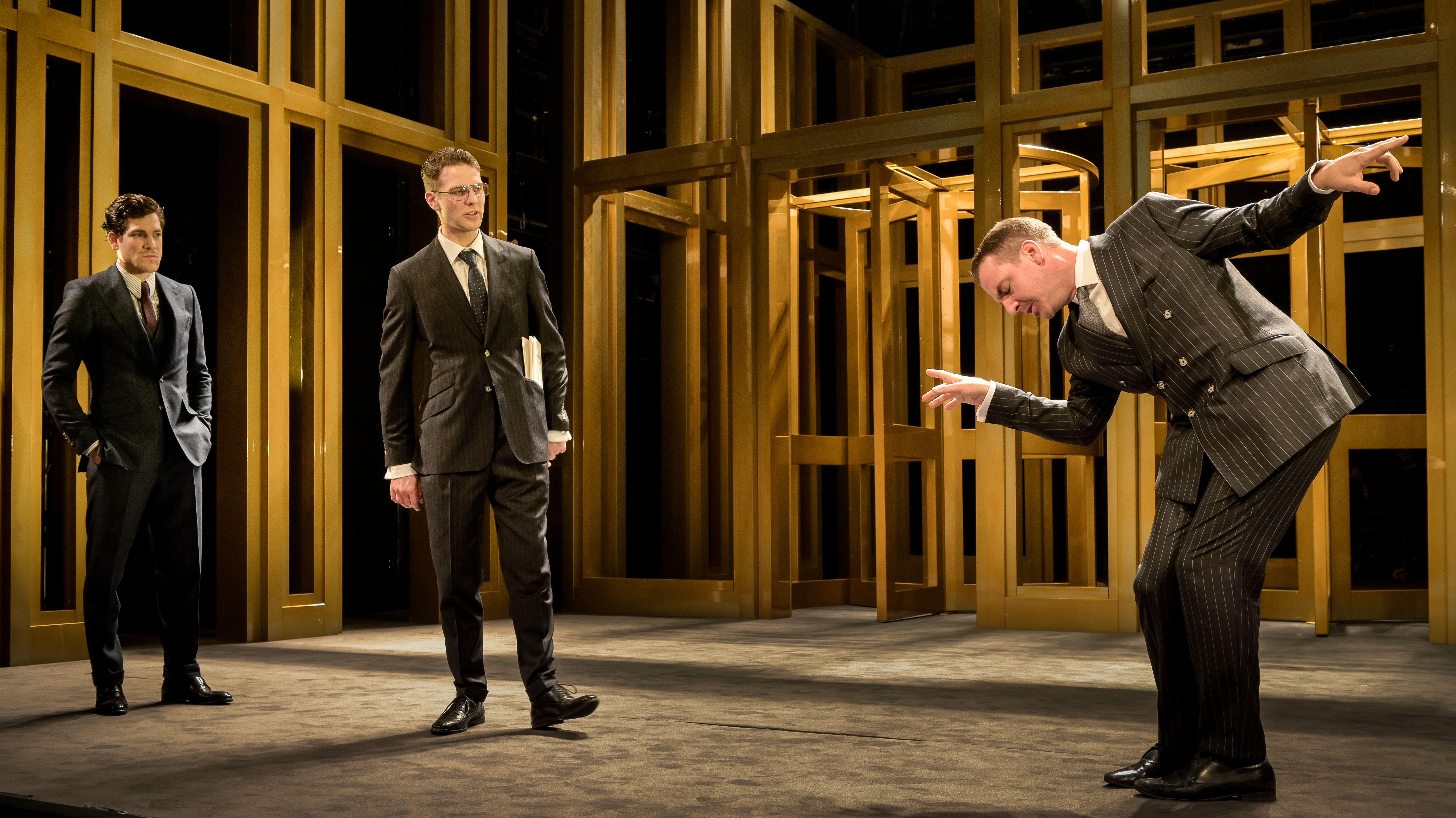 Jonathan Hutter, Silas Breiding und Pascal Fligg stehen im chicen Anzug auf der Bühne des Münchner Volkstheaters vor einer goldfarbenen Kulisse