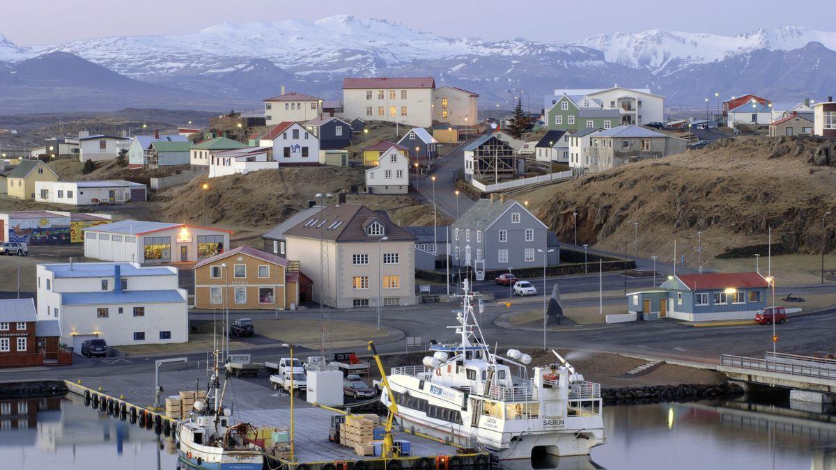 Im Vordergrund ein Steg mit Fischerboot und Fähre, dann ein kleines Dorf aus einfachen Häusern, im Hintergrund ein schneebedecktes Bergmassiv