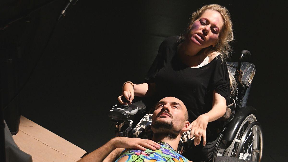 Lucy Wilke im Rollstuhl mit leidenschaftlich verzerrtem Gesicht, auf ihrem Schoß Paweł Duduś mit verträumtem Blick