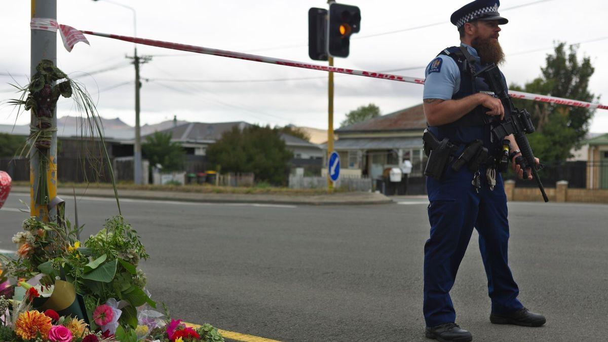 Christchurch, Neuseeland, 2019: Polizist steht neben Blumen, nach dem Anschlag auf eine Moschee