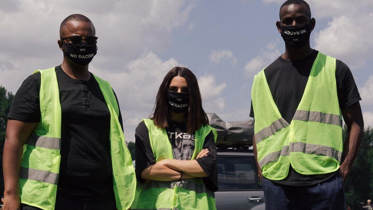 Drei junge Menschen mit schwarzer Maske und Warnweste stehen auf einer Wiese.