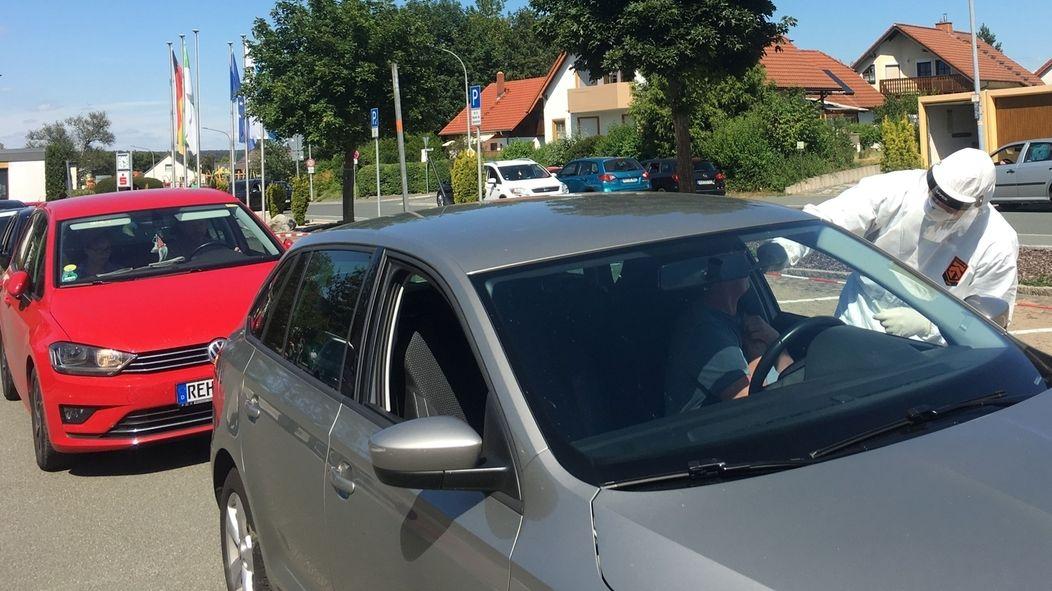 Autofahrern wird bei geöffnetem Seitenfenster Abstriche genommen, davor steht ein medizinischer Mitarbeiter in weißer Ganzkörperschutzkleidung.
