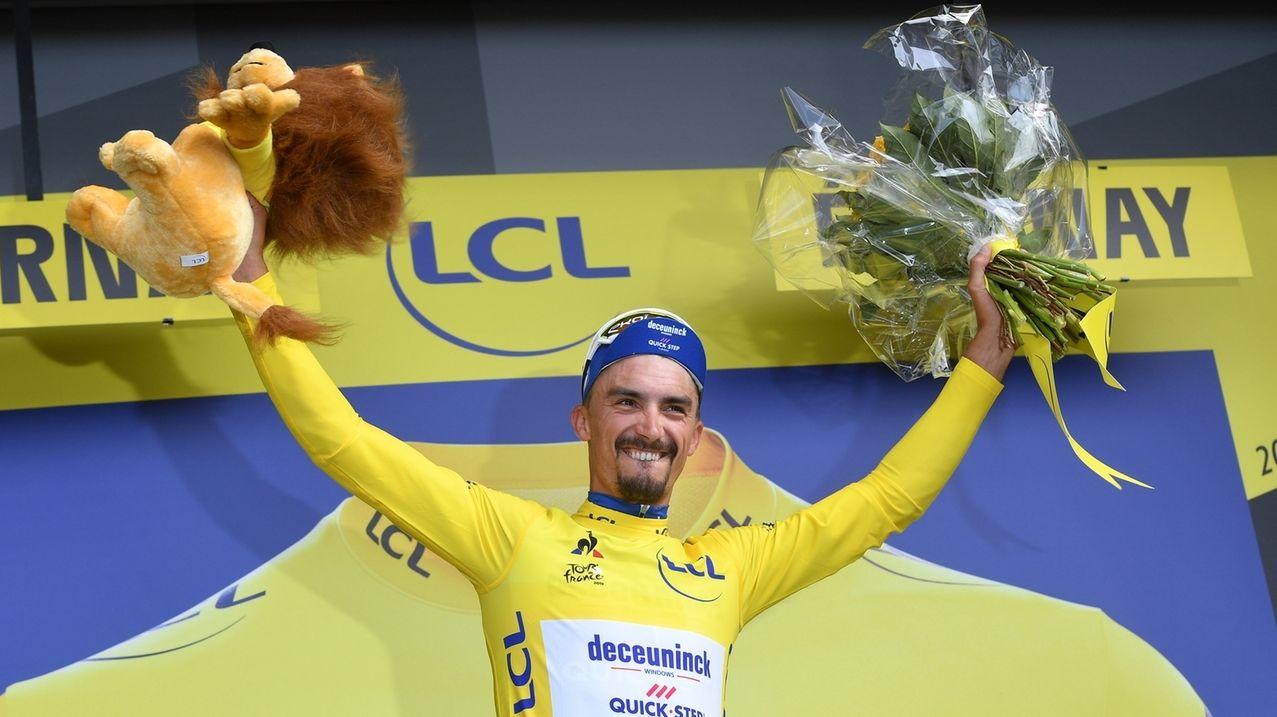 Der Franzose Julian Alaphilippe feiert nach seinem Etappensieg mit dem Gelben Trikot auf dem Podium.