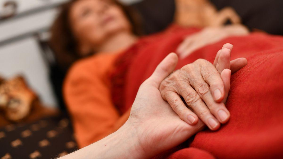 Ältere Frau liegt im Bett, ihre Hand wird gehalten.