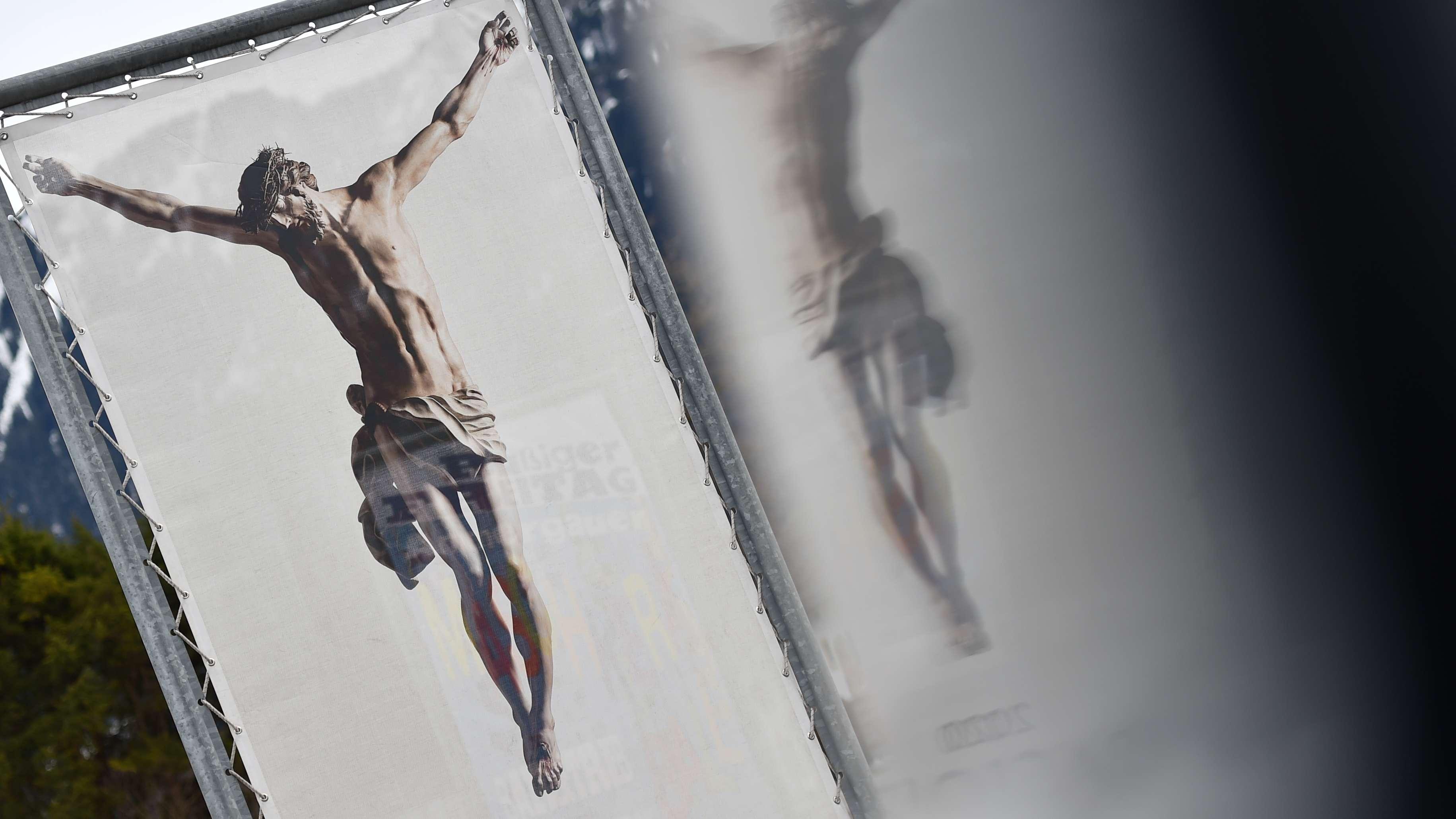 Oberammergau: Ein Werbeplakat für die Passionsspiele 2020 spiegelt sich in einen Autofenster.