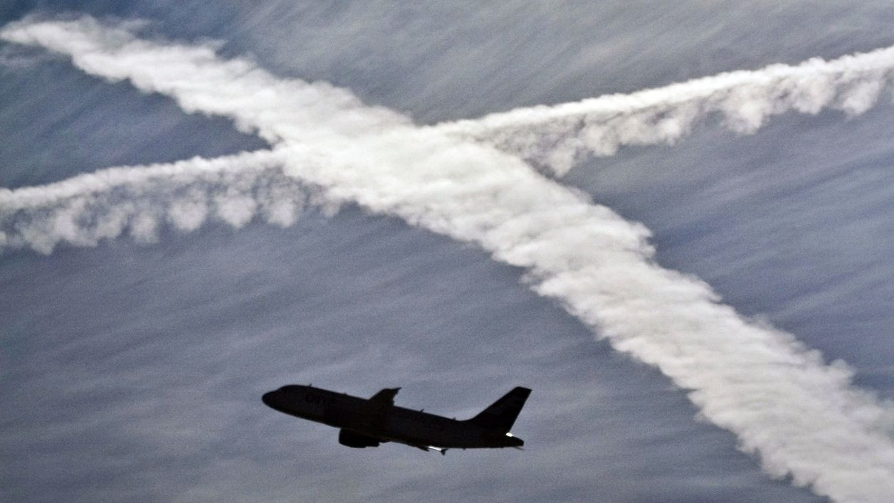 Flugzeug am Himmel, im Hintergrund Kondensstreifen, die sich kreuzen