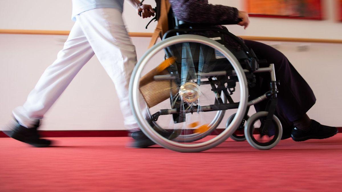 Pflegekraft schiebt alte Person in einem Rollstuhl über roten Teppichboden.
