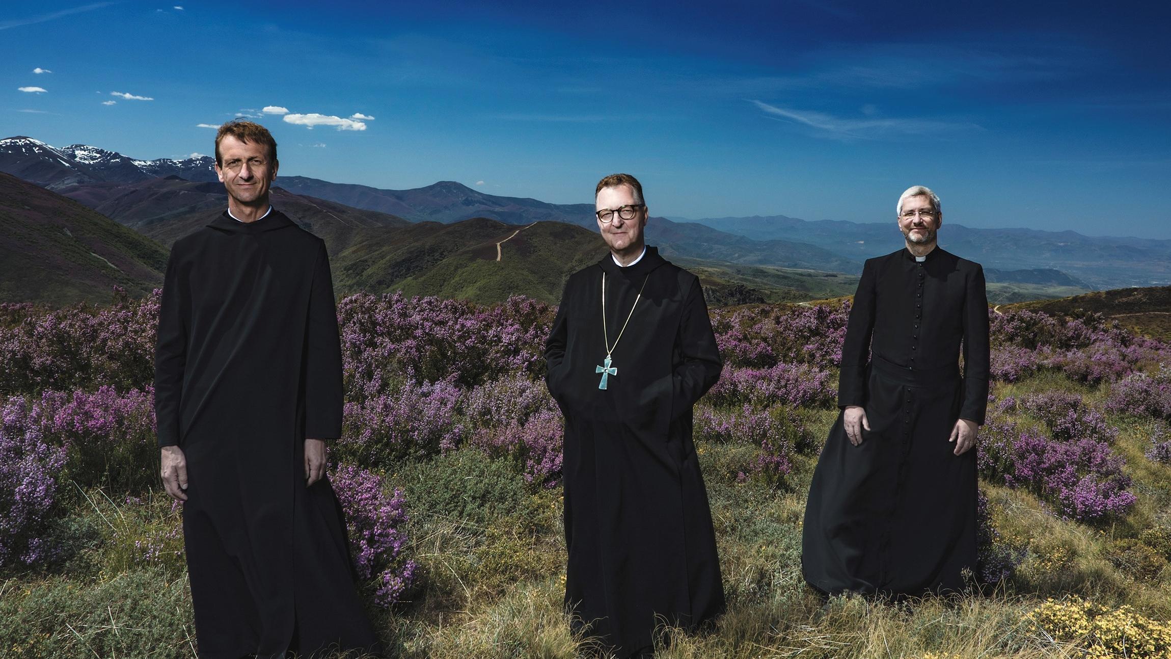 """Das Gesangstrio """"Die Priester"""" seht auf einem Berg in einer Wiese."""