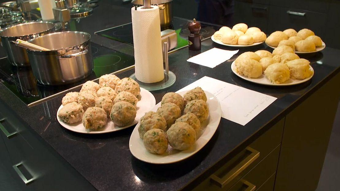 Viele Klöße liegen auf Tellern, die in einer Küche auf der Arbeitsplatte stehen.