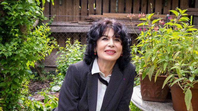 Frau mit schwarzen Haaren und Jackett in einem Garten sitzend