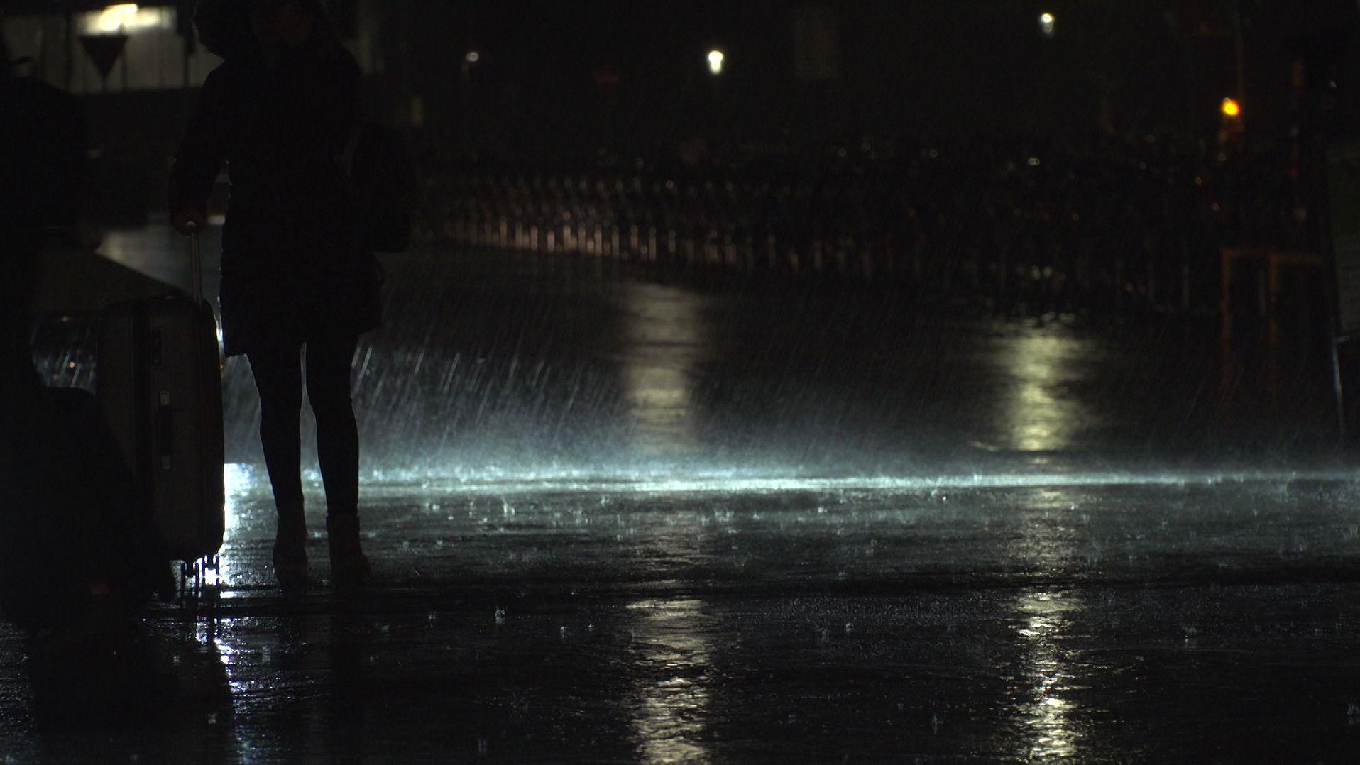 Person bei Nacht im Regen