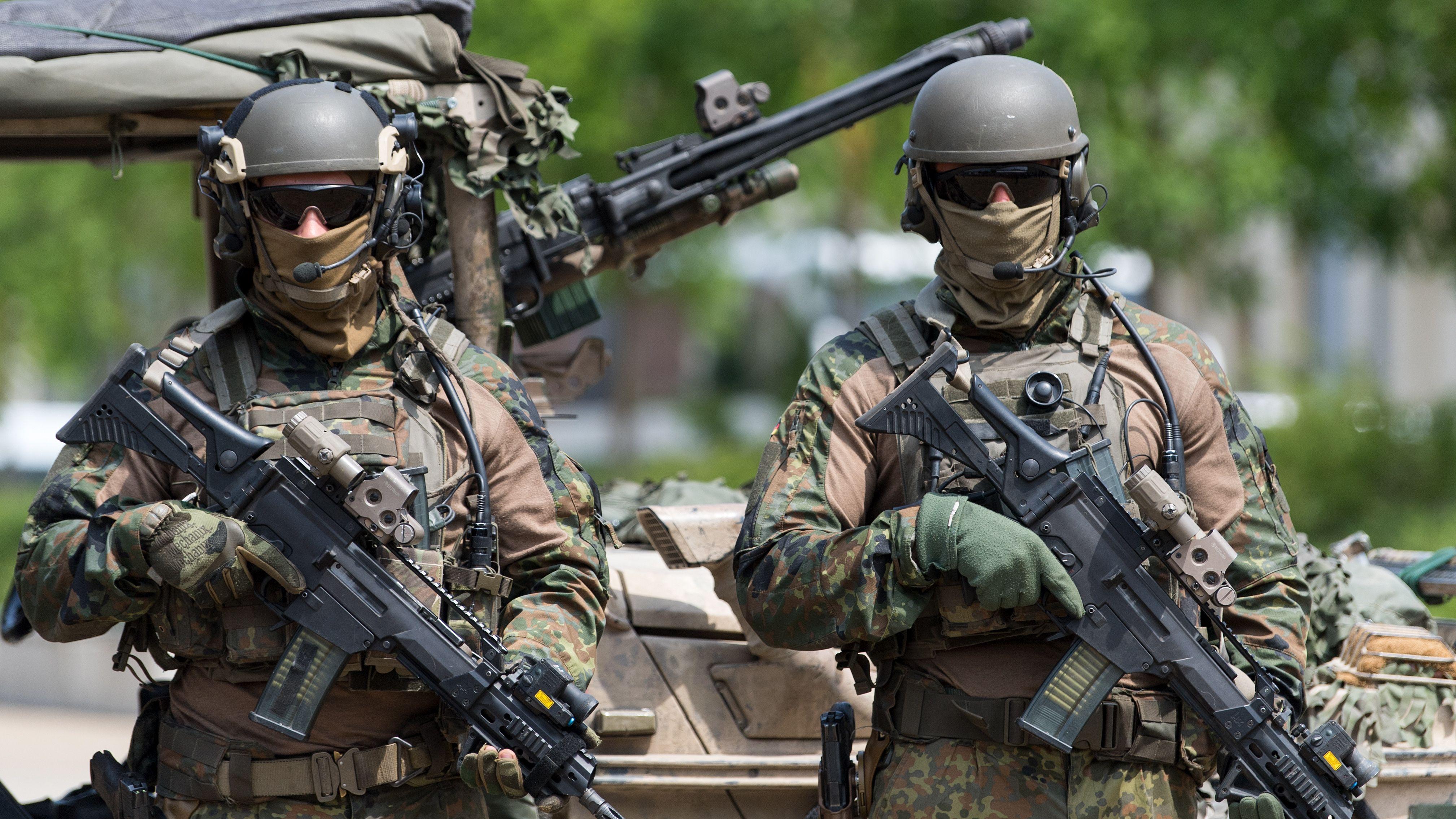 Zwei vermummte Spezialkräfte der Bundeswehr mit Maschinengewehren bewaffnet.