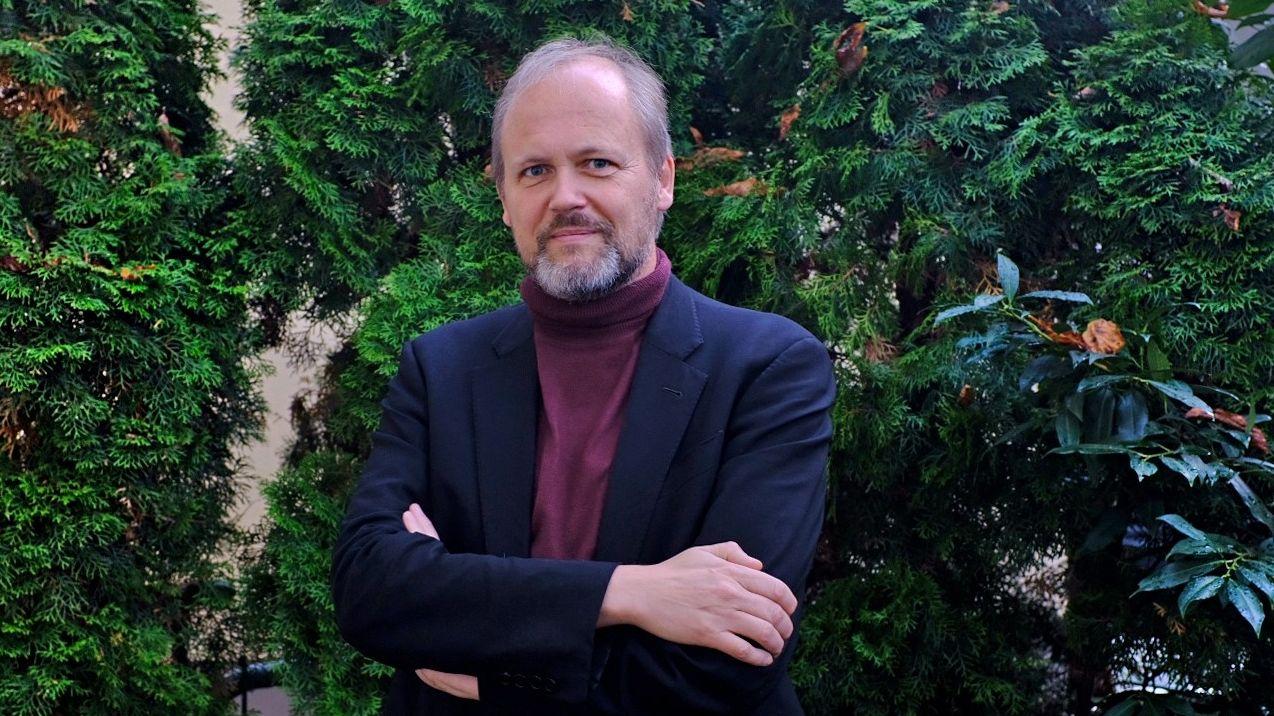 Wolfgang Ullrich blickt, vor einem Busch stehend, freundlich in die Kamera