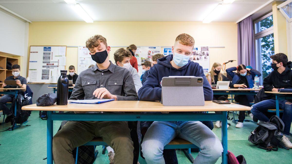 Schüler sitzen in einer Klasse mit Nasen-Mund-Bedeckung (Symbolbild)