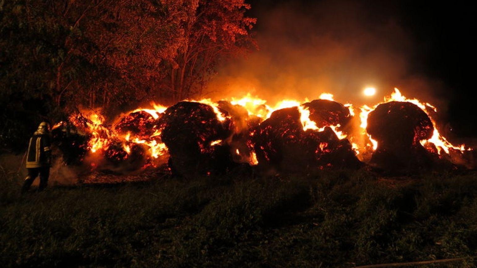 Ein Feuerwehrmann versucht, brennende Heuballen bei Bad Staffelstein