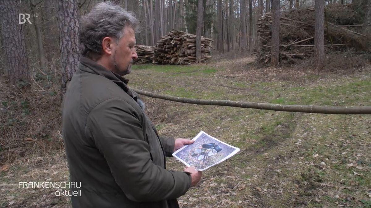 Förster Thomas Knotz steht im Wald und schaut auf ein Foto.