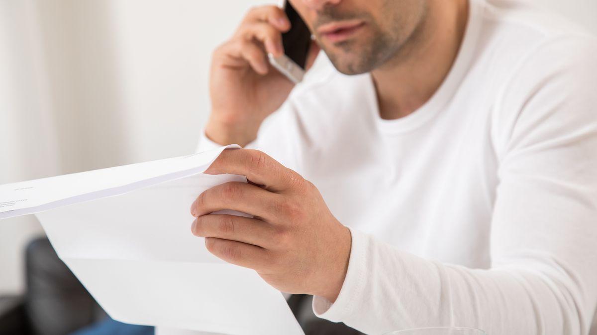 Ein Mann liest ein Papier und telefoniert dabei (Symbolbild).
