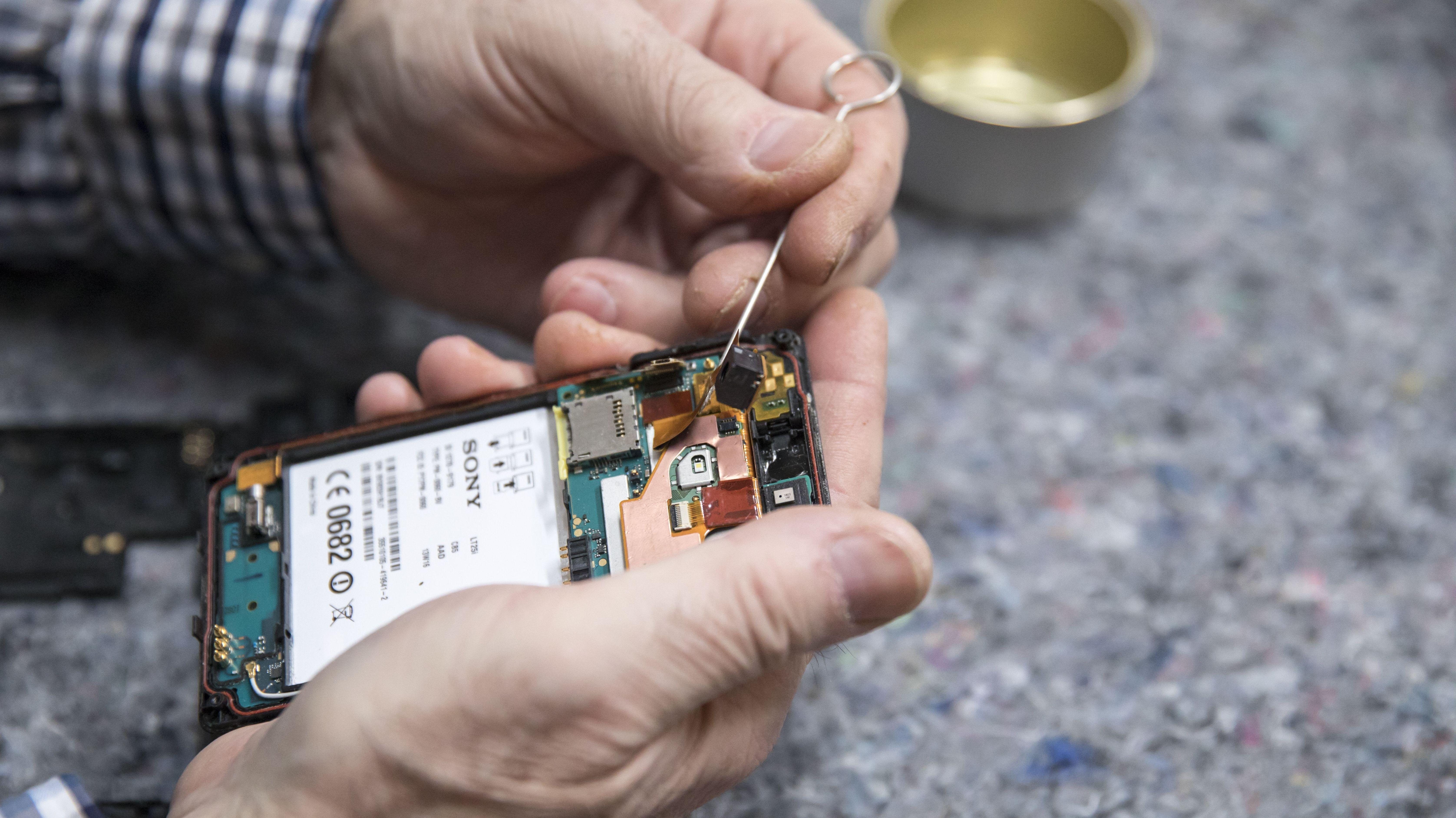 Mann repariert Smartphone.