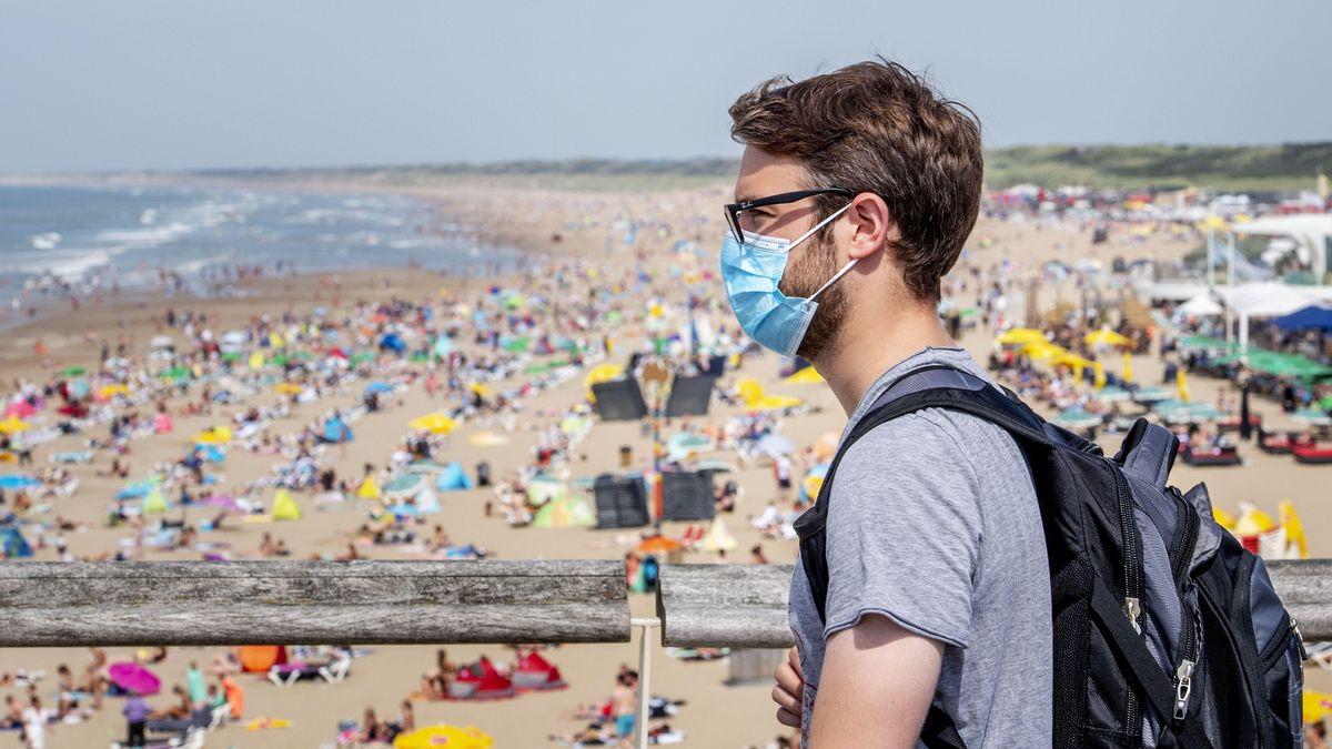 Ein Urlauber mit Maske am Stand