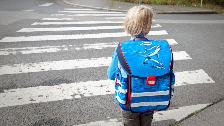 Ein Mädchen hält auf dem Schulweg an einem Zebrastreifen. (Symbolbild) | Bild:picture alliance/Jan Haas