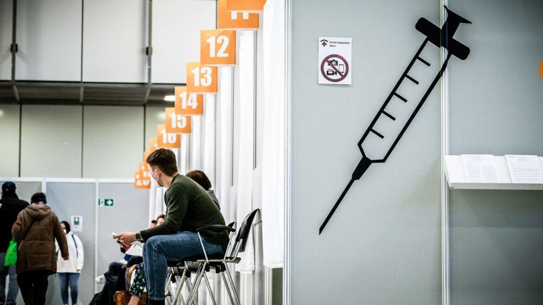 Menschen warten im Corona Impfzentrum Messe Berlin auf ihre Corona-Impfung.
