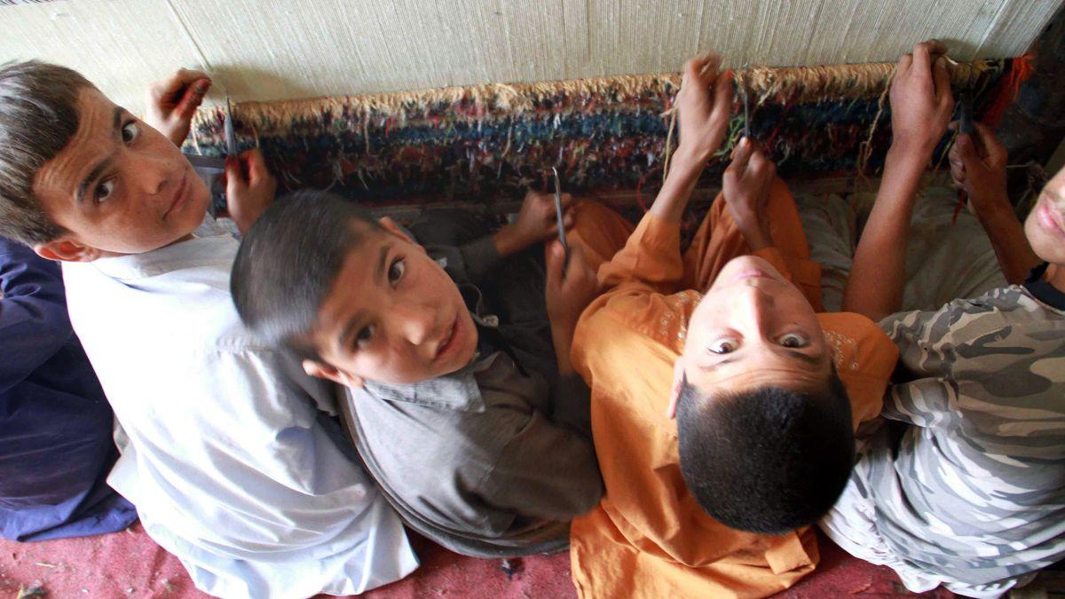 Kinder knüpfen einen Teppich.